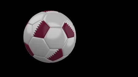 único : Soccer ball with the flag of Qatar flies past the camera, slow motion, 4k footage with alpha channel