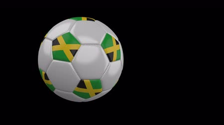 múlt : Soccer ball with the flag of Jamaica flies past the camera, slow motion, 4k footage with alpha channel Stock mozgókép