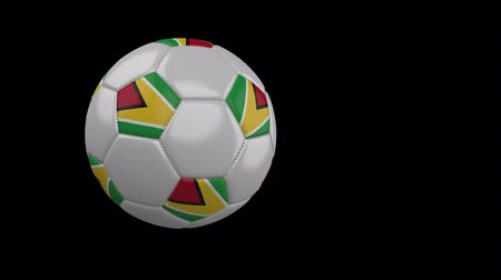 guyana : Soccer ball with the flag of Guyana flies past the camera, slow motion, 4k footage with alpha channel