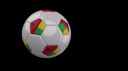 rotates : Soccer ball with flag Guinea Bissau flies past camera, slow motion blur, 4k footage with alpha channel