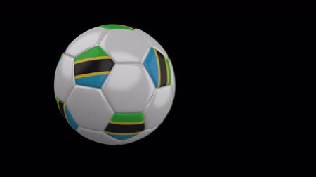 ações : Soccer ball with flag Tanzania flies past camera, slow motion blur, 4k footage with alpha channel