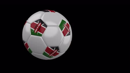 múlt : Soccer ball with flag Kenya flies past camera, slow motion blur, 4k footage with alpha channel Stock mozgókép