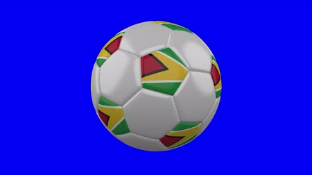 georgetown : Soccer ball with Guyana flag rotates on blue chroma key background, loop