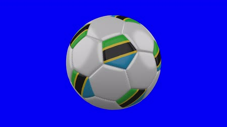 ações : Soccer ball with Tanzania flag rotates on blue chroma key background, loop Stock Footage