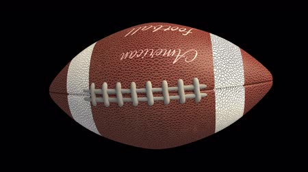 stilleven : Ball for American football with the inscription American football flies and rotates on transparent background, 4k alpha loop Stockvideo
