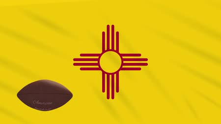 флаг : New Mexico flag and american football ball rotates against background of a waving cloth, loop Стоковые видеозаписи