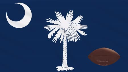 colômbia : South Carolina flag and american football ball rotates against background of a waving cloth, loop