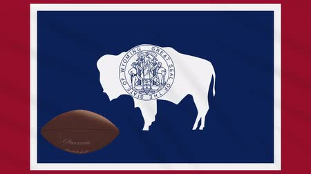 búfalo : Wyoming flag and american football ball rotates against background of a waving cloth, loop Stock Footage