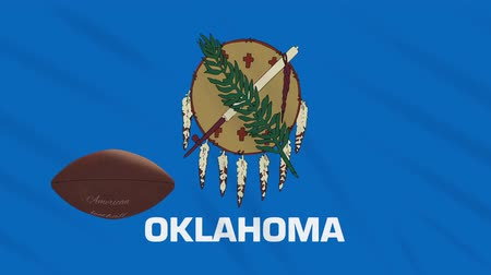 végső : Oklahoma flag and american football ball rotates against background of a waving cloth, loop
