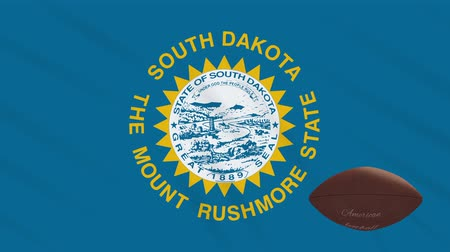 végső : South Dakota flag and american football ball rotates against background of a waving cloth, loop