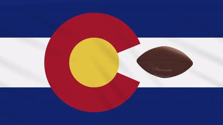 denver : Colorado flag and american football ball rotates against background of a waving cloth, loop Stock Footage