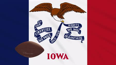 iowa : Iowa flag and american football ball rotates against background of a waving cloth, loop Stock Footage