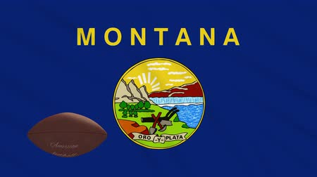 決勝 : Montana flag and american football ball rotates against background of a waving cloth, loop 動画素材