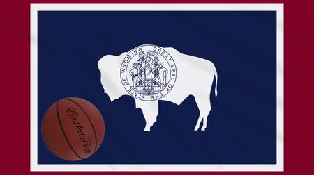 abroncs : Wyoming flag and basketball ball rotates against background of a waving cloth, loop