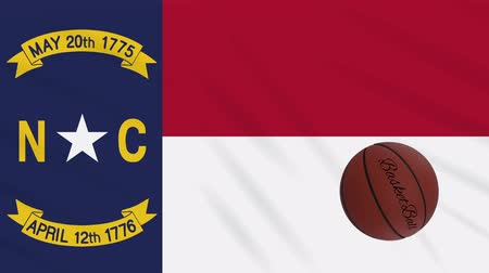 abroncs : North Carolina flag and basketball ball rotates against background of a waving cloth, loop