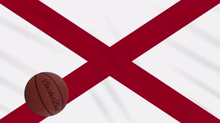 abroncs : Alabama flag and basketball ball rotates against background of a waving cloth, loop Stock mozgókép