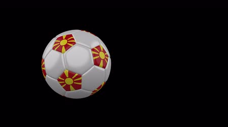 Republic of Northern Macedonia flag on a flying and rotating soccer ball on a transparent background, 4k prores footage with alpha channel Стоковые видеозаписи