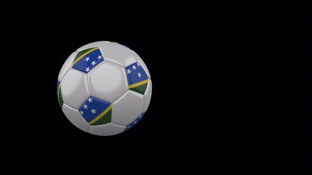 melanesia : Solomon Islands flag on a flying and rotating soccer ball on a transparent background, 4k prores footage with alpha channel