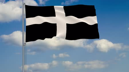 Flag of Kernow - Cornwall against background of clouds floating on the blue sky