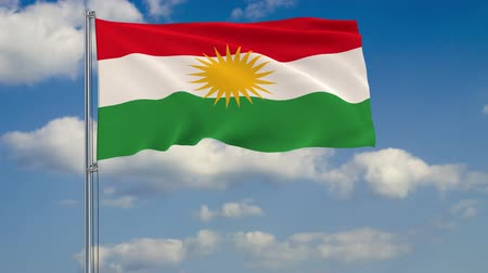 Flag of Kurdistan against background of clouds floating on the blue sky