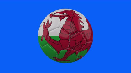 futball labda : Wales flag on a ball rotates on a transparent blue background, 4k prores footage with alpha transparency, loop