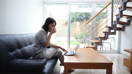 rests : Pretty young woman typing on laptop and drinking coffee at modern cozy home Stock Footage