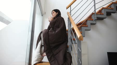 cobertor : Young beautiful woman covered with blanket drinking hot coffee sitting on stairs at home