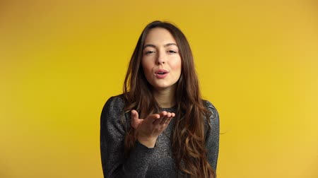 Woman flirting on yellow background. Emotions concept. Slow motion
