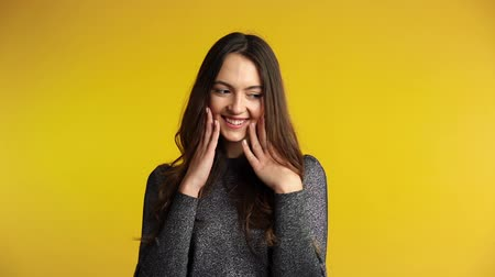 Shy coquette woman flirting and posing on yellow background. Emotions concept. Slow motion Стоковые видеозаписи