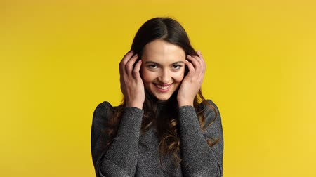 Shy coquette woman flirting and posing on yellow background. Emotions concept