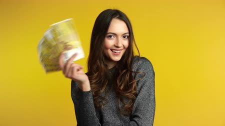 Happy young woman holding stack of money. Business, income, success concept.
