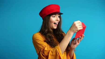 получать : Young happy woman opening gift card, she is excited and surprised. Emotions concept