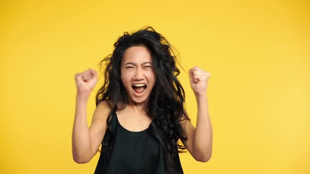 Asian woman screaming with arms up on yellow background. Negative emotions, hate, rage or stress concept. Slow motion