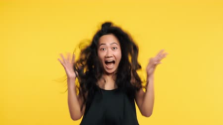 regozijo : Ecstatic asian woman jumping with joy celebrating success. Wow and happy emotions concept