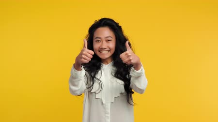 Happy asian girl showing thumbs up on yellow background. Positive, successful, approve, motivation gesture