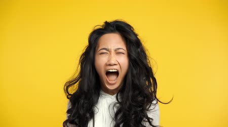 Angry asian woman screaming on yellow background. Negative emotions, hate, rage or stress concept. Slow motion