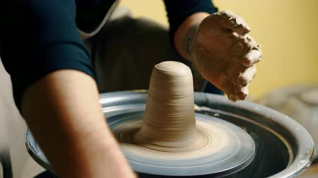 moldagem : Potter modeling ceramic pot from clay on a potters wheel.