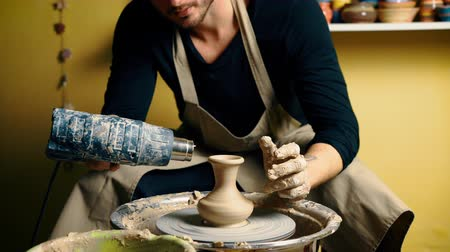 Professional male potter drying ceramic pot with special dryer in pottery workshop