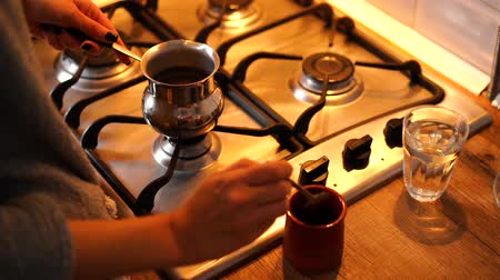 Woman make coffee in cezve in modern kitchen at home