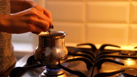 Female hand steering coffee in cezve over gas stove at kitchen