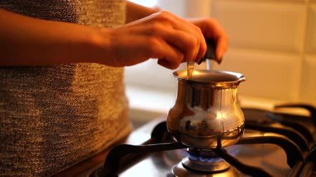 латте : Female hand steering coffee in cezve over gas stove at kitchen