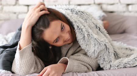 Playful young woman hiding under blanket and have fun in bed at home