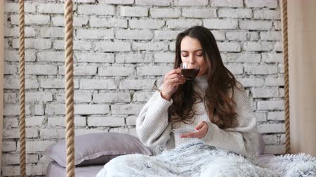 Young pretty woman drinking aroma coffee in bed at home