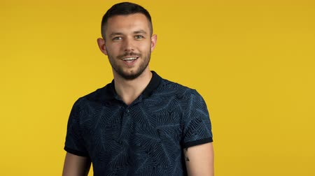 Young happy man coming to yellow background