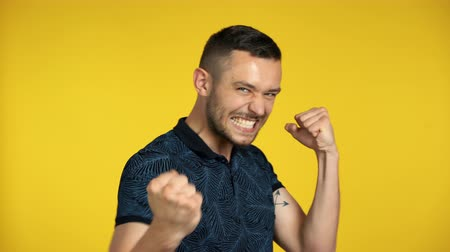 Happy excited man celebrate success isolated on yellow background