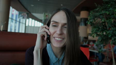 свободно : slowmotion - Young attractive woman calling with cell telephone while sitting alone in coffee shop during free time, attractive female with cute smile having talking conversation with mobile phone while rest in cafe