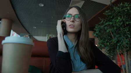 padlástér : slowmotion - Young business woman talking on the phone sitting in a cafe at lunch