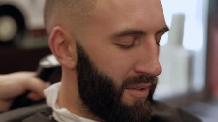 bigode : Close-up young bearded man getting head haircut by hairdresser at barbershop, slowmotion