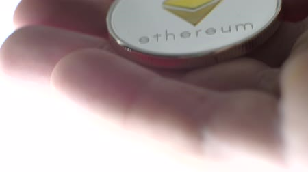 pergamen : Extreme close-up - Ethereum coin in the mans hand. Eth.