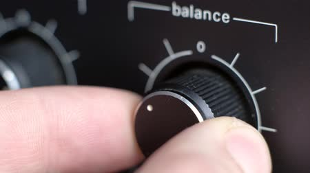 knob : close-up - sound engineer controls the volume balance of the old amplifier, turns adjustment audio frequency